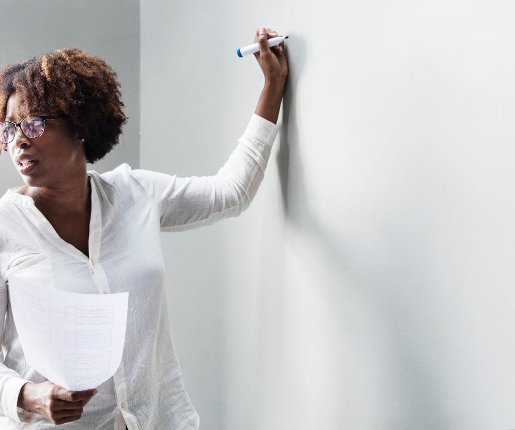 Photo of a woman at a whiteboard