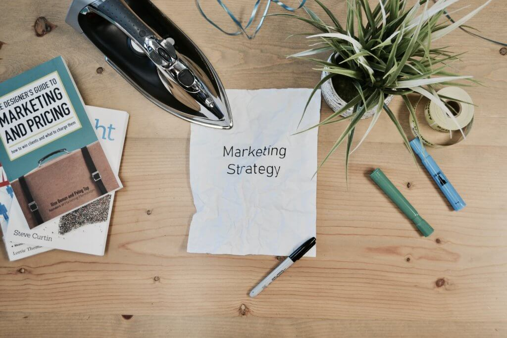 A piece of paper on a table tat says marketing strategy