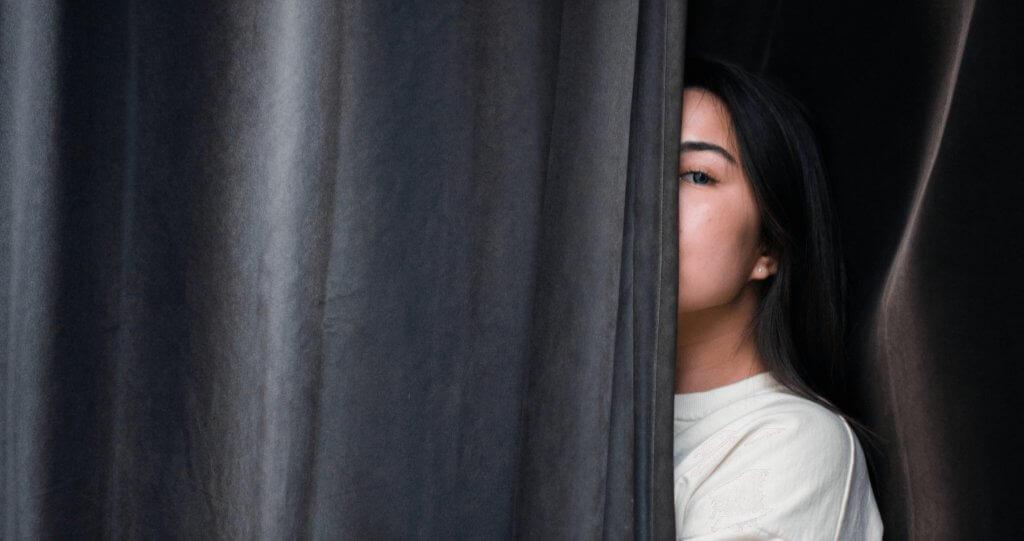 Woman hiding behind curtain